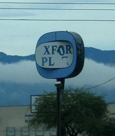 That awful sign, made more dramatic by mountain and cloud.
