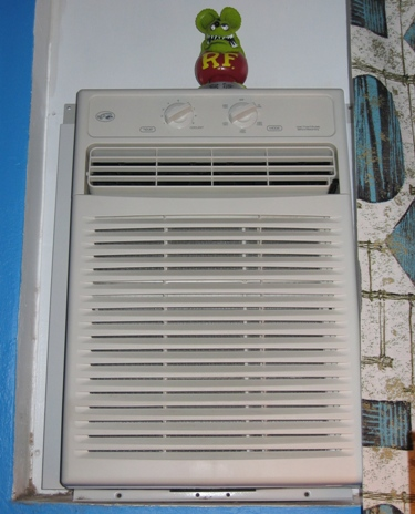 The bedroom A/C, abetted by vintage curtains and Rat Fink.